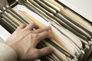 lawyer going through filing cabinet for legal documents